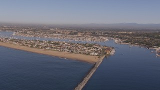 CAP_021_075 - HD stock footage aerial video of passing by the inlet to the bay by coastal neighborhoods, Newport Beach, California
