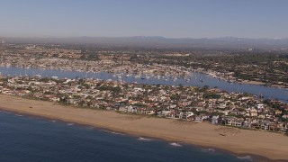 CAP_021_076 - HD stock footage aerial video of flying by the beach and bay by coastal neighborhoods, Newport Beach, California