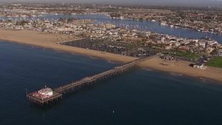 CAP_021_077 - HD stock footage aerial video approach and orbit pier by the beach and coastal neighborhoods, Newport Beach, California
