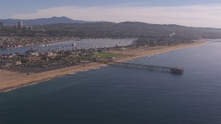 CAP_021_078 - HD stock footage aerial video fly away from pier by the beach and coastal neighborhoods, Newport Beach, California