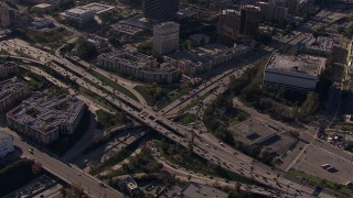 CAP_021_107 - HD stock footage aerial video orbit the 101 / 110 interchange with heavy traffic, tilt to reveal skyline, Downtown Los Angeles, California