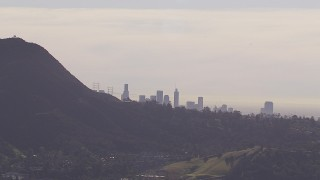 CAP_021_130 - HD stock footage aerial video of the city's skyline on a hazy day, eclipsed by the Hollywood Hills, Downtown Los Angeles, California