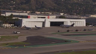 CAP_021_133 - HD stock footage aerial video of civilian jets and helicopters by a Burbank Airport hangar, California
