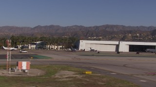 CAP_021_134 - HD stock footage aerial video of civilian jets and helicopters by aviation building and a Burbank Airport hangar, California