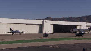 CAP_021_136 - HD stock footage aerial video of passing civilian jets and helicopters by a Burbank Airport hangar, California