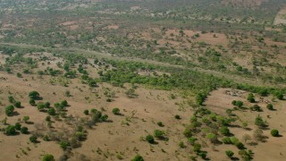 CAP_026_013 - HD stock footage aerial video of approaching a village across a dry river in open savanna, Zimbabwe