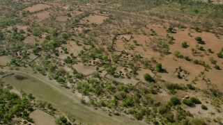 CAP_026_014 - HD stock footage aerial video approach and tilt to a village in open savanna, Zimbabwe