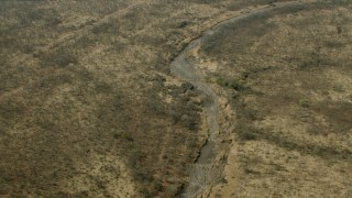 CAP_026_022 - HD stock footage aerial video of tilting to a dry riverbed in the savanna, Zimbabwe