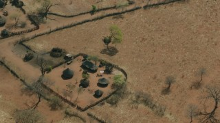 CAP_026_025 - HD stock footage aerial video of orbiting and flying away from a small village in the savanna, Zimbabwe