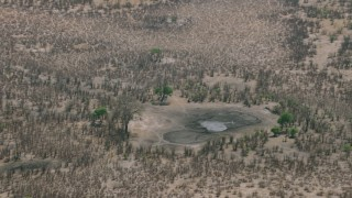 CAP_026_039 - HD stock footage aerial video of orbiting a nearly dry pond in the savanna, Zimbabwe
