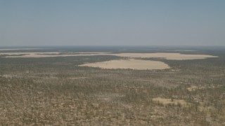 CAP_026_042 - HD stock footage aerial video of flying by clearings in the trees and brush in the savanna, Zimbabwe