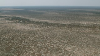 CAP_026_048 - HD stock footage aerial video of approaching trees and brush around a shallow river in the open savanna, Zimbabwe