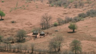 CAP_026_059 - HD stock footage aerial video of orbiting huts and fields in a small village, Zimbabwe