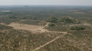 CAP_026_062 - HD stock footage aerial video of flying toward hills beside fields with view of savanna, Zimbabwe