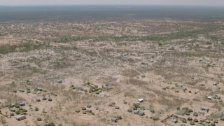 CAP_026_069 - HD stock footage aerial video of flying over a village with the savanna in the distance, Zimbabwe