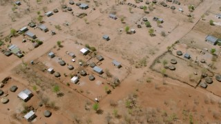 CAP_026_071 - HD stock footage aerial video of tilting to a bird's eye view of huts in a village, Zimbabwe