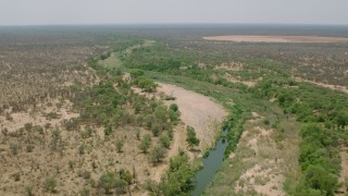 CAP_026_073 - HD stock footage aerial video of following a narrow river past trees in savanna, Zimbabwe