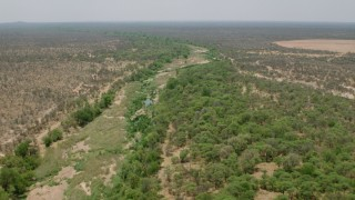 CAP_026_074 - HD stock footage aerial video of following a nearly dried up river past trees in savanna, Zimbabwe