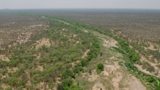 CAP_026_075 - HD stock footage aerial video of flying over a dry riverbed past trees in savanna, Zimbabwe