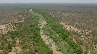CAP_026_076 - HD stock footage aerial video of following a dry riverbed past trees in savanna, Zimbabwe