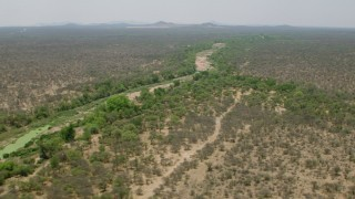 CAP_026_077 - HD stock footage aerial video of flying by a dry riverbed and trees in savanna, Zimbabwe