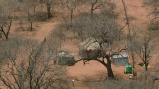 CAP_026_084 - HD stock footage aerial video of orbiting a wooden hut in the village, Botswana