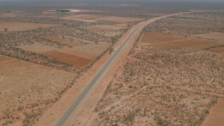 CAP_026_092 - HD stock footage aerial video approach and tilt to a bird's eye of the road outside the village, Botswana