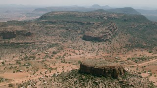CAP_026_100 - HD stock footage aerial video of orbiting a village beside green mountains in Zimbabwe