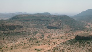 CAP_026_101 - HD stock footage aerial video of passing a village beside green mountains in Zimbabwe