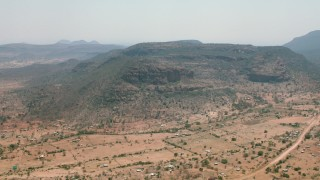 CAP_026_102 - HD stock footage aerial video of a village beside green mountains in Zimbabwe