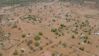CAP_026_115 - HD stock footage aerial video of flying over an African village, tilt to the houses below, Zimbabwe