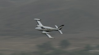 CBAX01_003 - HD stock footage aerial video of tracking a Cessna 340 in flight, overcast day, Perris, California