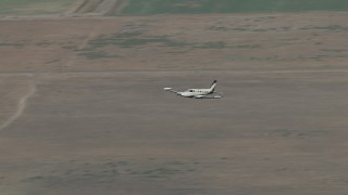 CBAX01_007 - HD stock footage aerial video of tracking Cessna 340 in flight over farmland, hazy, Perris, California