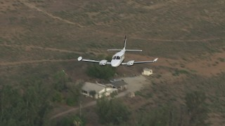 CBAX01_009 - HD stock footage aerial video of flying over rural neighborhood, revealing Cessna 340, Perris, California