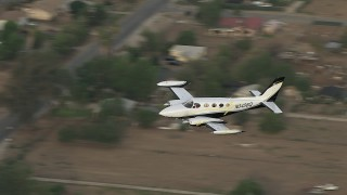 CBAX01_010 - HD stock footage aerial video of tracking Cessna 340 over rural neighborhood, Perris, California