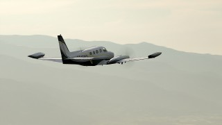 CBAX01_016 - HD stock footage aerial video of tracking Cessna 340 over hills on hazy day; Perris, California