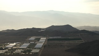 CBAX01_017 - HD stock footage aerial video fly by farmland, hills, reveal Cessna 340 flying into frame, hazy, Perris, California