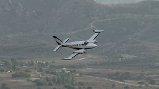 CBAX01_019 - HD stock footage aerial video of tracking Cessna 340 over hazy, rural countryside, Perris, California