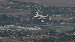 CBAX01_020 - HD stock footage aerial video of tracking Cessna 340 entering frame, flying over rural town, Perris, California