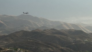 CBAX01_021 - HD stock footage aerial video of flying by hazy hills, revealing Cessna 340 entering frame, Perris, California
