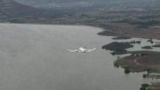 CBAX01_024 - HD stock footage aerial video of tracking Cessna 340 over Lake Mathews, hazy, Perris, California