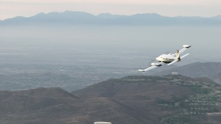 CBAX01_025 - HD stock footage aerial video of flying by hazy hills, revealing Cessna 340, Perris, California