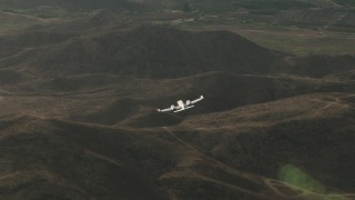 CBAX01_028 - HD stock footage aerial video of tracking Cessna 340 over hills then out of frame on hazy day, Perris, California