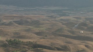 CBAX01_029 - HD stock footage aerial video of a Cessna 340 flying across hazy hills, Perris, California