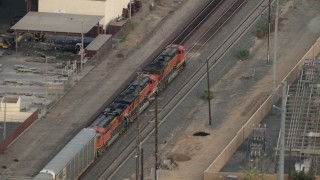 CBAX01_035 - HD stock footage aerial video of a train passing through town, Corona, California