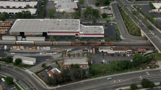 CBAX01_036 - HD stock footage aerial video of train passing through commercial area, Corona, California