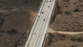 CBAX01_047 - HD stock footage aerial video of tracking light traffic on Highway 71, brown hills, Chino Hills, California