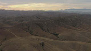 CBAX01_049 - HD stock footage aerial video of flying over mountain range, partly cloudy, Chino Hills, California