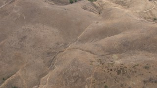 CBAX01_052 - HD stock footage aerial video of a bird's eye view of a dry mountain range, scattered trees, Chino Hills, California