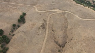 CBAX01_053 - HD stock footage aerial video of dirt paths in mountain range with scattered vegetation, Chino Hills, California